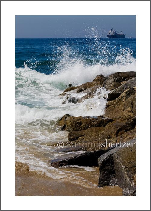 Waves crash on a rock jetty along the California coast line.