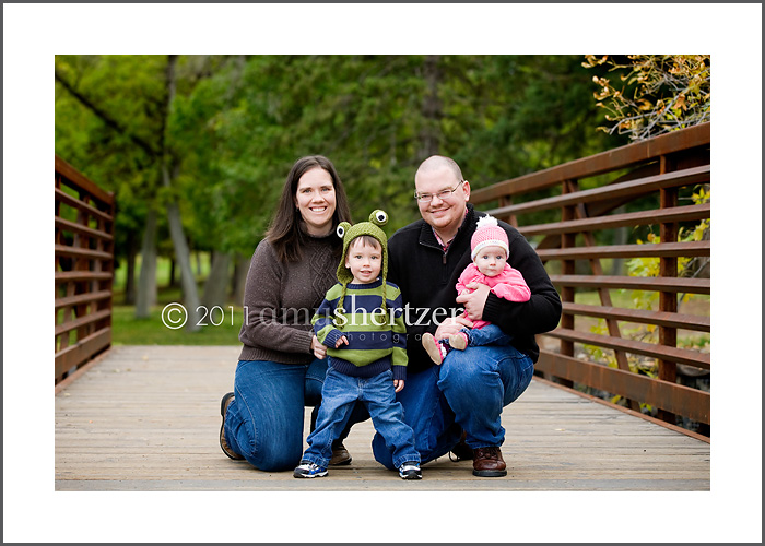 A Bozeman Montana family poses for a portrait with a lush green backdrop.