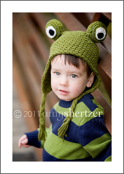 A 2 year old poses for a portrait with an adorabel froggie hat.
