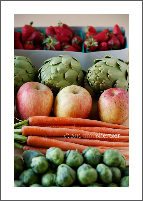 Fresh carrots, apples, artichokes, strawberries, and brussels sprouts look delicious.