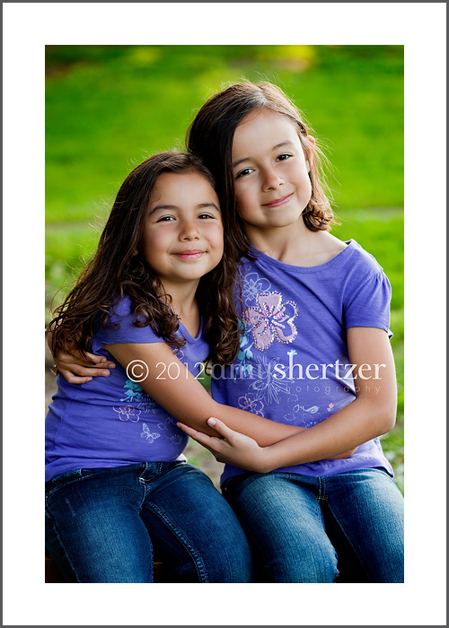 Adorable sisters in purple shirts give each other a sweet hug for a picture in Los Angeles..