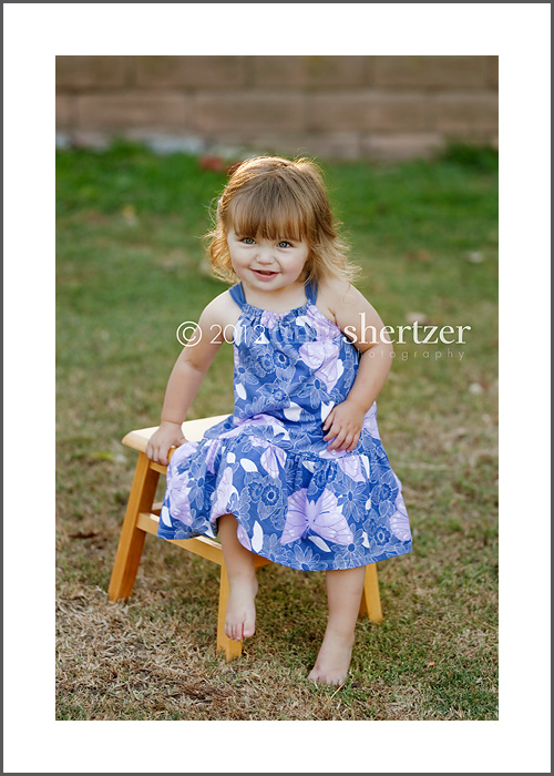 A toddler girl in a purple dress poses for a portrait in El Segundo.