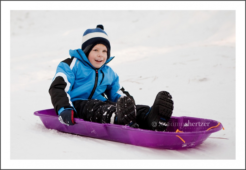 A boy in a blue jacket smiles as he sleds down a hill.