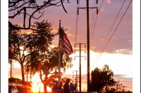 The setting sun makes a warm glow in the sky and through an American flag.