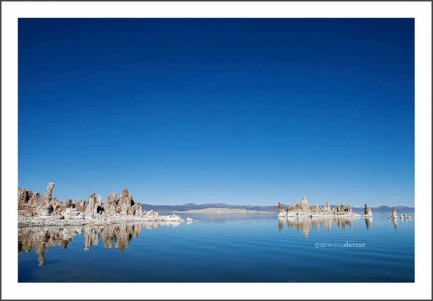 Tufas of Mono Lake cast a perfect reflection on a smooth blue lake.