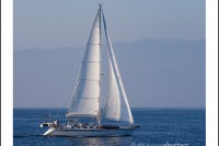 White sails of a beautiful sail boat in a blue ocean off the coast of Ventura California.